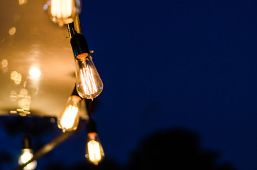 Vintage antique hanging light bulbs at a street food market. Holidays and business good idea concept.