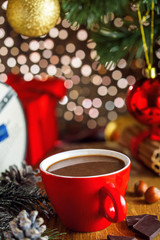 Hot chocolate mug, Christmas tree and gift boxes on background. Traditional sweet winter cocoa drink.