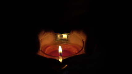 burning candle in the hands of women.