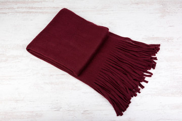 Woolen winter scarf on a white wooden background