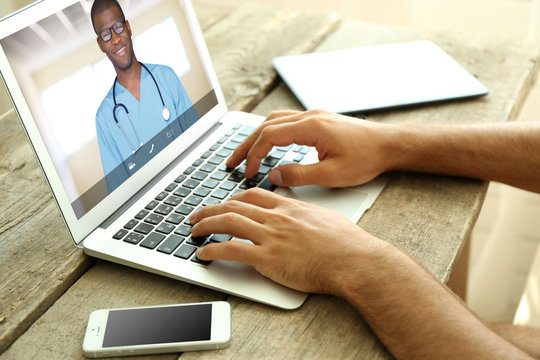 Man video chatting with doctor on laptop. Professional medical online consultation concept.
