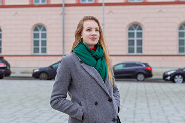 Beautiful and young girl in a coat walks on the daily city