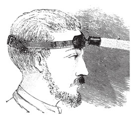 Man with electric light attached to strap on forehead, vintage e