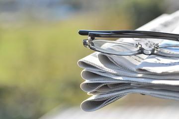 積み重なった新聞とメガネ