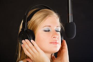 Woman singing to microphone wearing headphones in studio