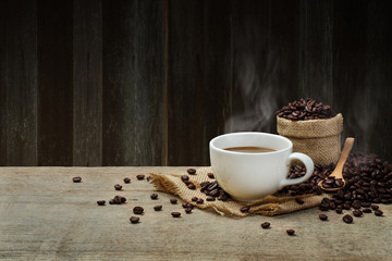 Hot Coffee cup with Coffee beans on the wooden table and the woo
