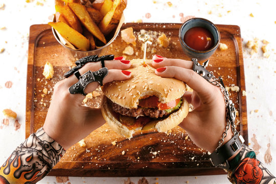 girl eating burger with beef tomato and lettuce