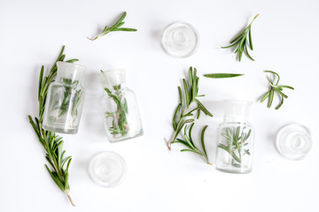fresh rosemary with bottle on white background top view