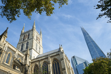 London skyline featuring the old architecture of the Southwark Cathedral with the modern Shard skyscraper beyond