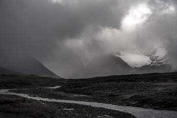 Glacier covered in sun lighted mist in river landscape black and white, Sweden