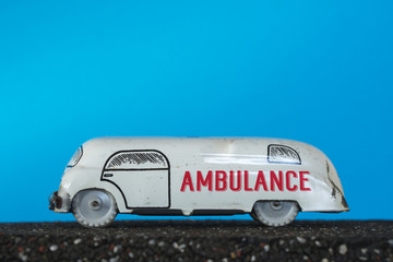Ambulance vintage toy car on blue background