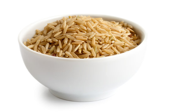 Bowl of long grain brown rice isolated on white.