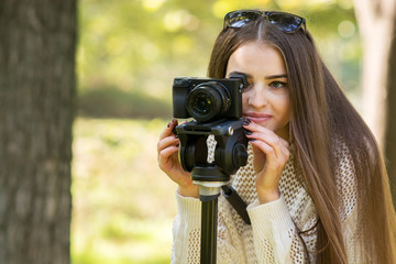 Young woman with photo camera in park taking pictures