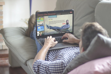 Young man lying comfortably on the sofa while using the laptop with video on demand website on the screen. View from behind. All screen graphics are made up.