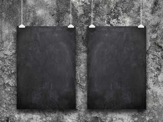 Two blank blackboard frames hanged by clips against dark weathered concrete wall background
