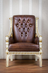 Brown and gold chair with wallpaper background