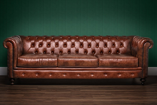 Brown chesterfield sofa with green wallpaper background