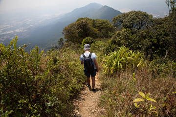 Hiker with backpack standing on top of a mountain. Vietnam, Dalat. travel concept