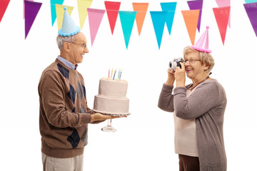 Mature woman taking picture of elderly man celebrating his birth
