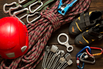 climbing and travel equipment on dark wooden background, top vie