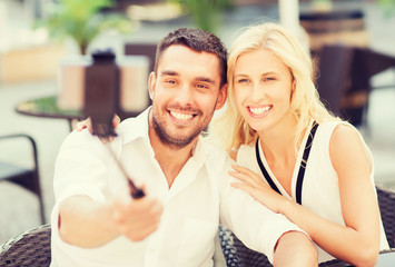 happy couple taking selfie with smartphone at cafe