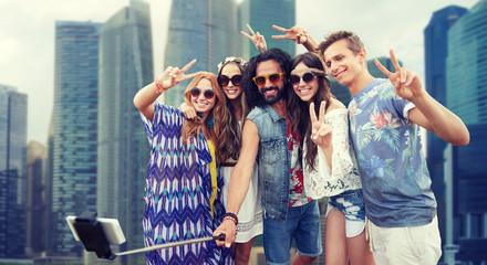 hippie friends with smartphone selfie stick
