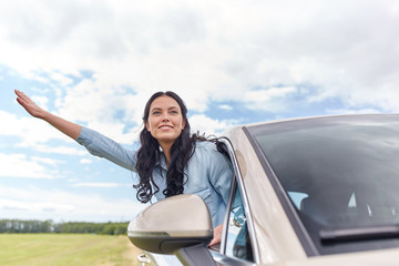 happy young woman driving in car and waving hand