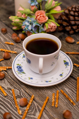 Small white cup of coffee, hazelnuts, cocoa beans, cookies and bouquet of flowers on wooden background