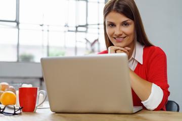 frau sitzt entspannt zu hause mit ihrem laptop und einer tasse tee
