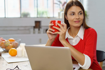 frau sitzt entspannt am laptop und genießt eine tasse tee