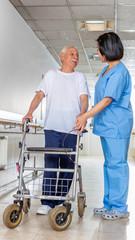 Asian nurse helping elder man with walker at hospital. Rehabilit