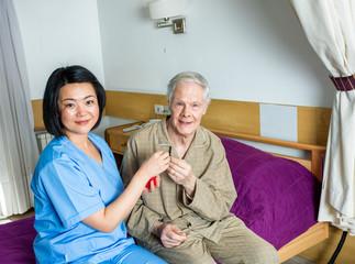Asian nurse handing medical pill to elder man in hospital bed