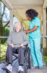Afroamerican nurse happy with caucasian elder patient on wheelch
