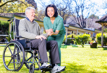 Asian nurse happy with caucasian elder patient on wheelchair, ou