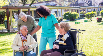Afroamerican nurse joking with elder disabled people outdoor