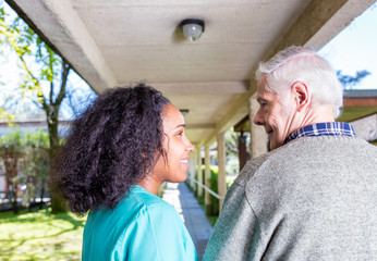 Afroamerican nurse helping elder man in hospital garden