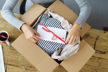 frau packt ein paket mit kleidung aus