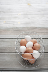 White and brown eggs in a wire basket. Weathered wood table. Copy space . Hazy, dreamy.