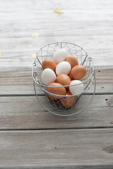 White and brown eggs in a wire basket. Weathered wood table. Copy space