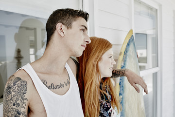 Young couple with surfboard standing in front of beach house looking at distance