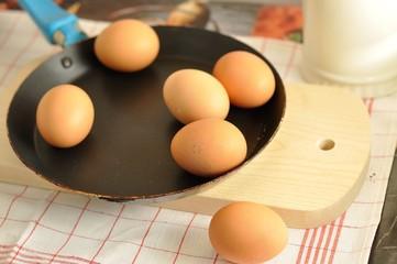 Raw brown eggs on pan