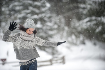 Happy woman wearing knitwear dancing in the snow