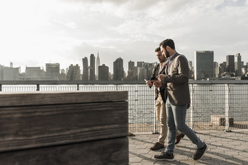 USA, New York City, two businessmen walking along East River looking at cell phone