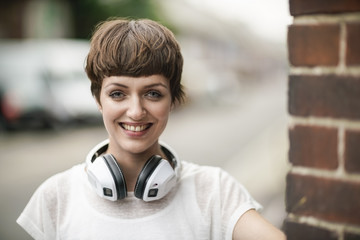 Portrait of happy young woman with short brown hair and white headphones