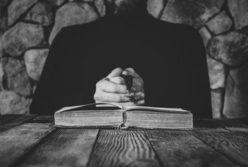 a man in black clothes with a prayer beads in hand praying in front of an old open book. the concept of praying, and studying. selective focus, black & white photo