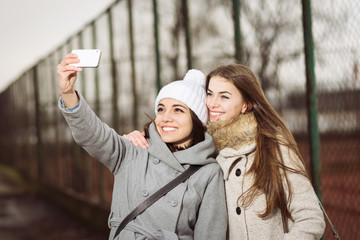 Two teenage girls in autumn outdoors taking a selfie