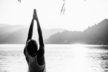 Sun Salutation Pose. Female doing yoga by the lake