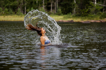 Beautiful girl splashing her hear in an Swedish forest lake