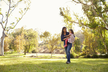 In de dag Ontspanning Asian Caucasian woman carrying her young daughter in a park