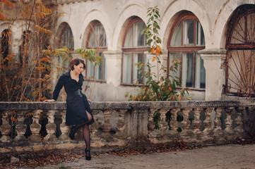 Молодая женщина в черном пальто стоит возле заброшенного старинного здания с колоннами
